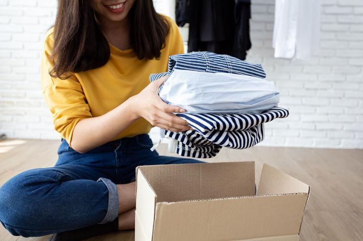 A young smiling woman packing clothes into a cardboard box