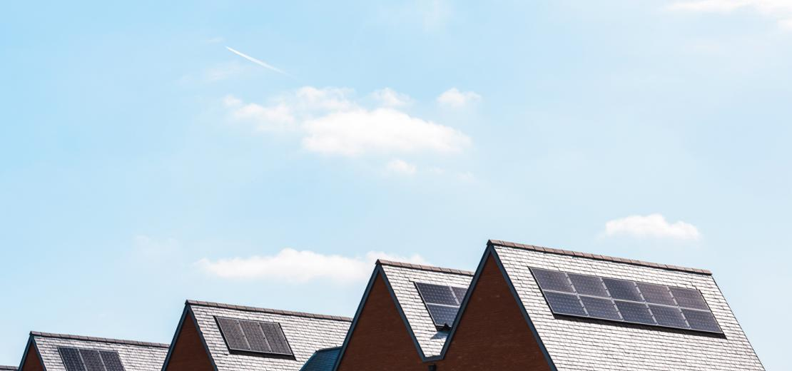 Rooftops of houses with solar panels on them.